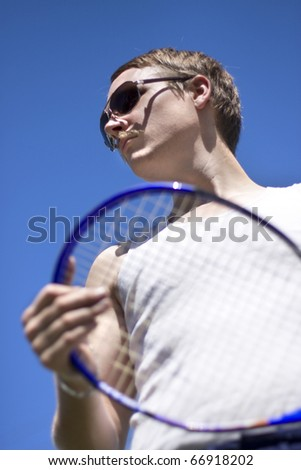 Tennis Player Sporting A Racquet And Pair Of Sunglasses - stock photo