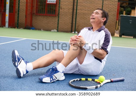 tennis player suffering a knee injury - stock photo