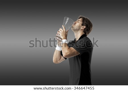 Tennis player tennis player with a black shirt, celebrating with a glass trophy, on a black background.