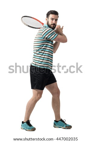 Tennis player waiting to hit ball holding racket with both hands in backhand pose. Full body length portrait isolated over white studio background. - stock photo