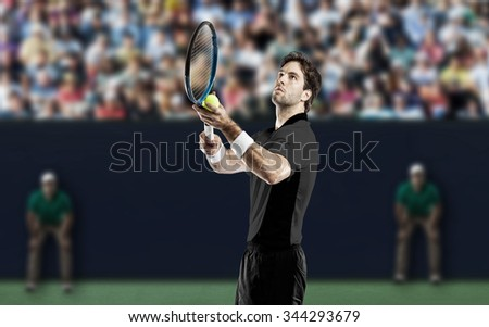 Tennis player with a black shirt, playing on a fast tennis court. - stock photo