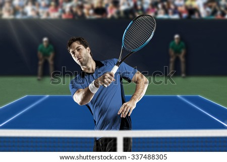 Tennis player with a Blue shirt, playing on a fast tennis court.