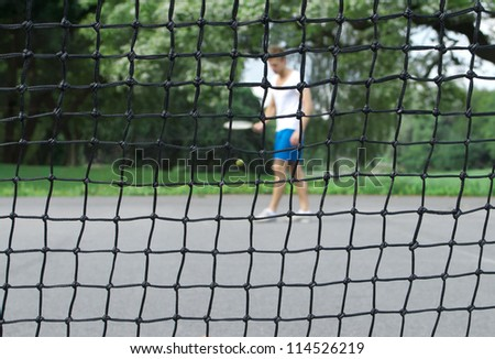 Tennis player with racket and ball seen through the tennis net. Focus on the net. - stock photo