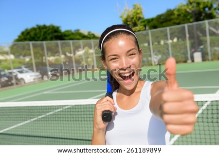 Tennis player woman giving thumbs up happy and excited looking at camera. Successful winning female athlete living healthy active sport fitness lifestyle outdoors in summer on tennis court. - stock photo