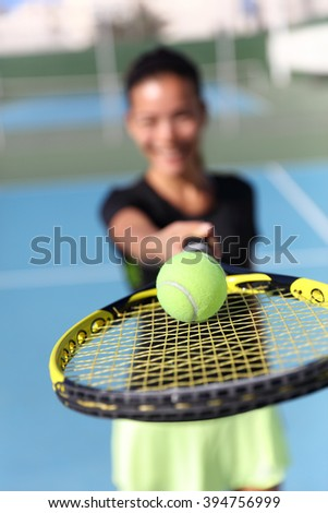 Tennis player woman showing ball on racket. Unrecognizable female athlete holding fitness equipment - closeup of yellow ball on outdoor summer court. Sport activity.