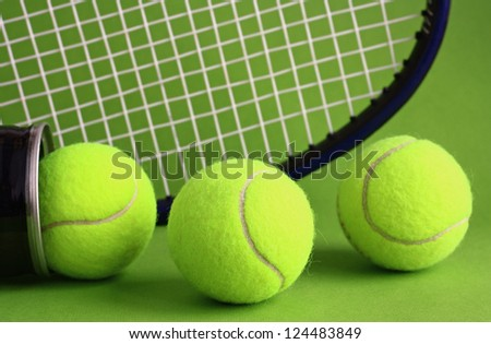 Tennis racket and ball on a green background. - stock photo