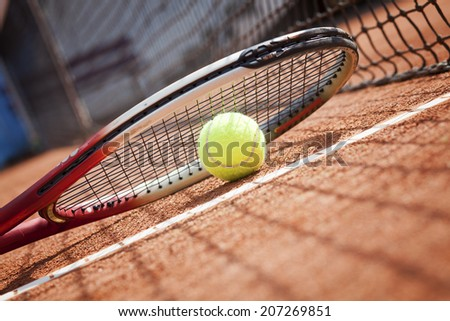 tennis racket and ball on the clay tennis court - stock photo