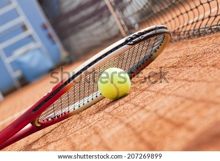 tennis racket and ball on the clay tennis court