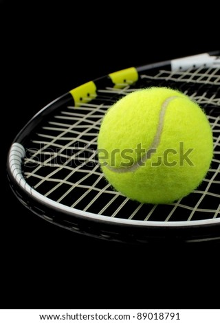 Tennis racket and tennis ball on black background - stock photo
