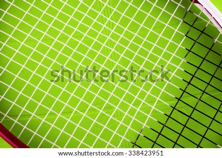 Tennis racket over green plastic field, close up, horizontal image - stock photo