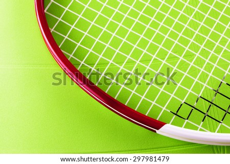 Tennis racket over green synthetic surface, horizontal image - stock photo