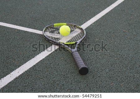Tennis racket (racquet) and ball on white T line of a tennis court - stock photo