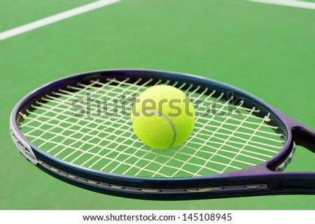 Tennis racket with ball on hard surface court - stock photo