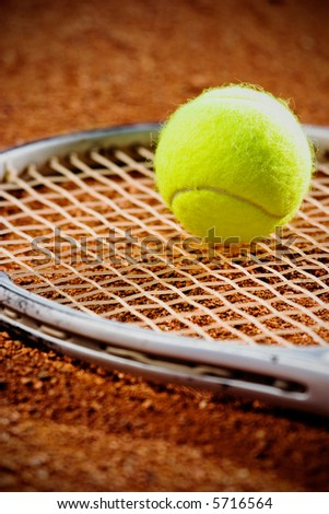 Tennis racket with ball  on it clay on clay court - stock photo