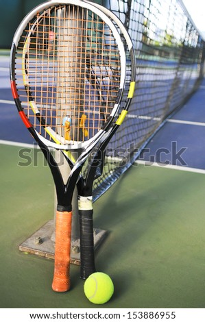 Tennis rackets and ball against the net - stock photo