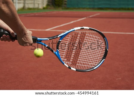 tennis racquet and ball on court background