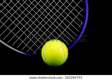 Tennis racquet and tennis ball isolated against a black background - stock photo