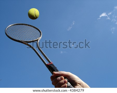 Tennis return with racket against blue sky. - stock photo