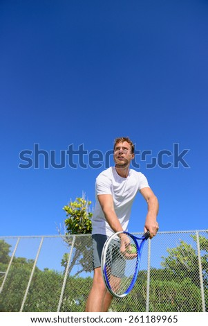 Tennis serve - man tennis player serving playing tennis outside in summer. Fit male athlete practicing. Healthy active sport lifestyle. - stock photo