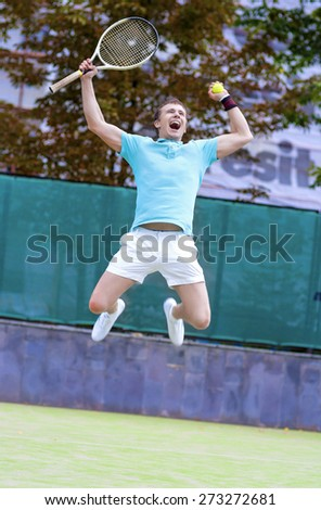 Tennis Sport Concept: Portrait of young Exclaiming Male Caucasian Tennis Player With Racket Outdoors on Court.Vertical Image Composition - stock photo