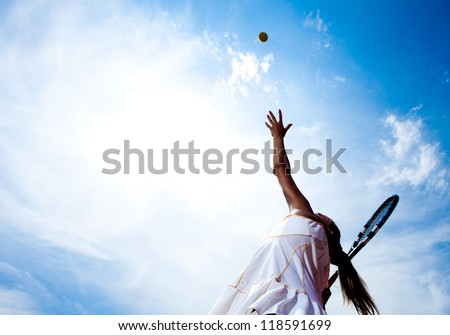 Tennis woman in a white tennis dress developing ball service - stock photo
