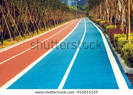 Tens of kilometers of marked curved bidirectional red cycling paths and blue running routes in the city. Streets are situated close to river and along road are deployment beautiful trees and bushes. - stock photo
