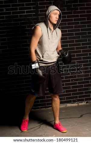 Tense young boxer waiting for his fight standing in his gear and gloves wearing a hoodie watching expectantly to be called - stock photo
