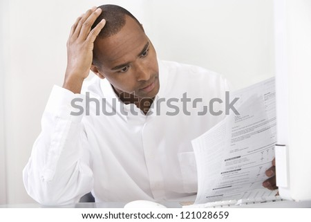 Tensed African American male executive with paperwork - stock photo