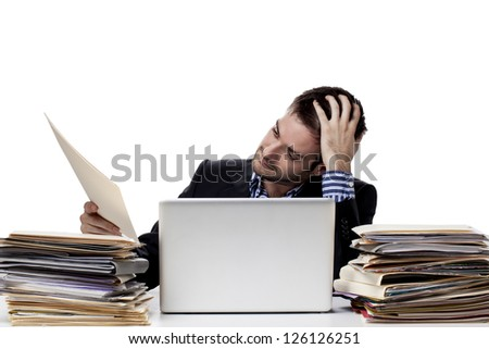 Tensed businessman looking at a report while at work - stock photo