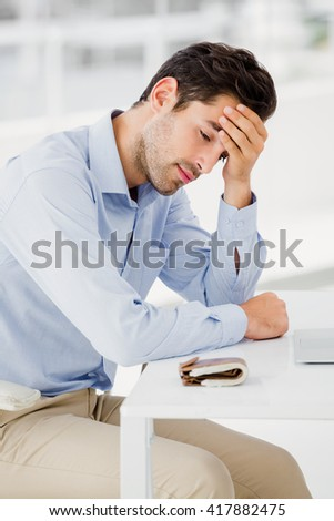Tensed businessman sitting at table with hand on forehead in office - stock photo