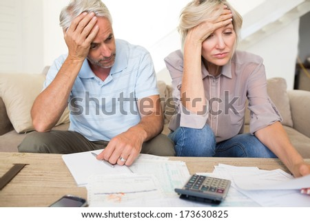 Tensed mature man and woman with bills and calculator sitting on sofa at home