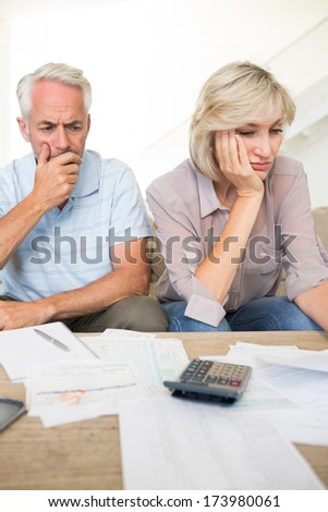 Tensed mature man and woman with bills and calculator sitting on sofa at home - stock photo