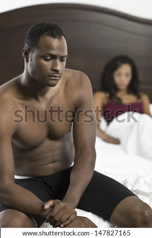 Tensed shirtless African American man sitting on bed with blurred woman in background - stock photo