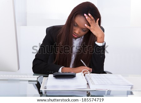 Tensed young businesswoman calculating tax at desk in office - stock photo