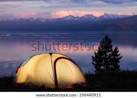 Tent across beautiful sunset on lake - stock photo