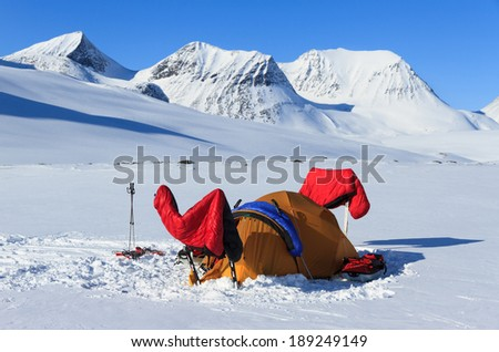Tent and sleeping bags drying in the sun in snow covered Lapland. - stock photo