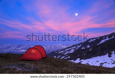 Tent at a mountain campsite in the Alps during an beautiful evening. - stock photo