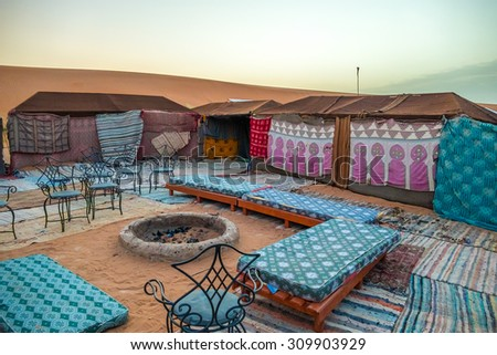 Tent camp for tourists in sand dunes of Erg Chebbi at dawn, Morocco - stock photo