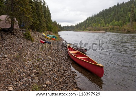 Tent camp in boreal forest and canoes on paddle river trip on McQuesten River, Yukon Territory, Canada - stock photo