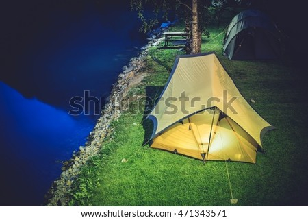 Tent Camping at Night. Two Large Tents on the Campsite. Waterfront Campground.