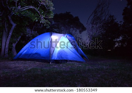 Tent glows at night during camping holiday or vacation in the country. - stock photo