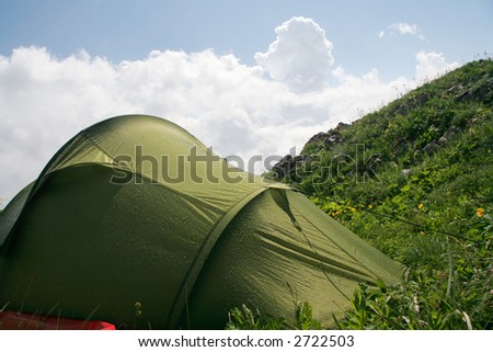 tent in mountains after rain - stock photo