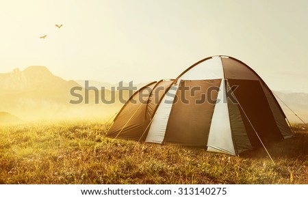 Tent in the mountains at sunset - stock photo