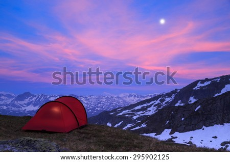 Tent in the mountains during a beautiful, cloudy evening. - stock photo