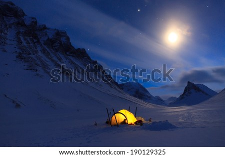 Tent in the snow covered mountains of Lapland on a beautiful winter night with moon and stars. - stock photo