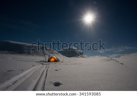Tent in the Snow unter the Moon  - stock photo