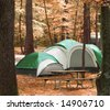 tent located between trees in the woods - stock photo