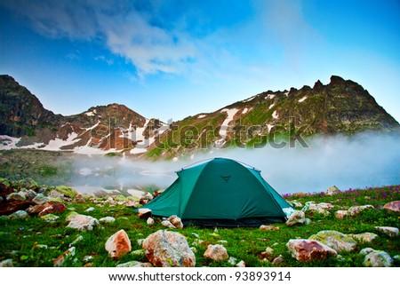 Tent near mountain lake - stock photo