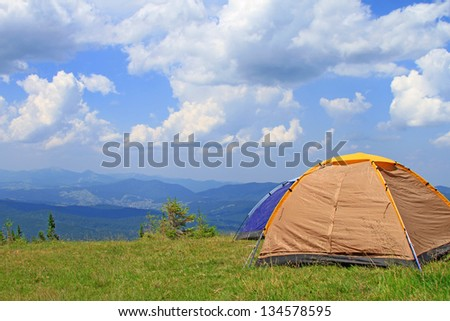 Tent of tourists on a green slope - stock photo