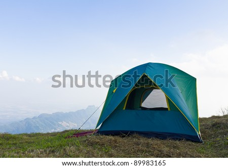 Tent on a grass under white clouds and blue sky - stock photo